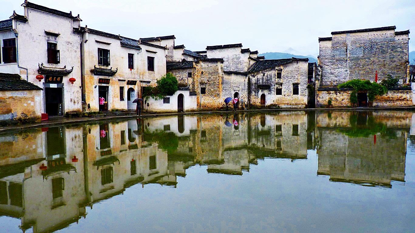 Inverted reflections of traditional houses lining Moon Pond in Hong Village, near Huangshan, China